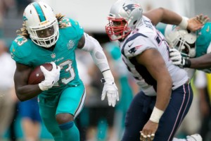 Miami Dolphins running back Jay Ajayi (23) looks for running room against the Patriots at Sun Life Stadium in Miami Gardens, Florida on January 3, 2016. (Allen Eyestone / The Palm Beach Post)